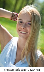 Outdoors portrait of young smiling woman (teenager) - hand behind head