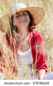outdoors relaxation - smiling beautiful older woman sitting in high dry summer field to enjoy peace under sun hat,summer daylight