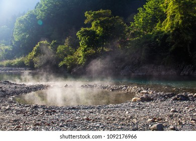 An outdoors river side natural hot spring pool onsen with steam rising from it in morning sun, in Kawayu,  Hongu, Wakayama, on the Kii Peninsula, at the end of the Kumano Kodo hiking trail, Japan.