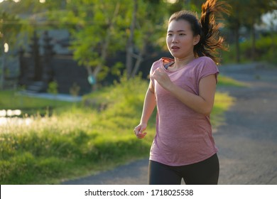 outdoors running workout - young happy and dedicated Asian Japanese woman jogging at beautiful city park or countryside trail on sunset enjoying fitness and cardio activity in healthy lifestyle