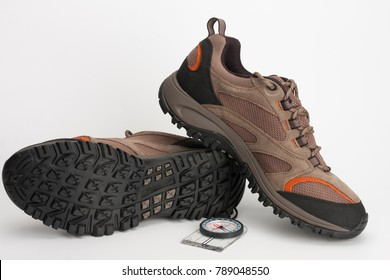 Outdoors shoes for man for hiking, trekking, climbing and walking and magnetic compass, studio shoot on white background