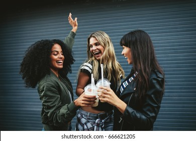 Outdoors shot of young women toasting with ice coffee on city street. Multiracial group of female friends having fun with ice coffee.