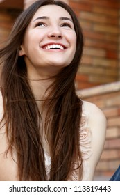 Outdoors street portrait of beautiful young brunette happy smiling teen girl