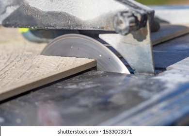 outdoors. sunny day. a man in yellow gloves saws a tile for the floor. machine with special circles.