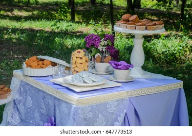 Outdoors there is a table decorated with purple tablecloths and flowers to Seregno. On the table, dishes in the style of Provence and a variety of sweets