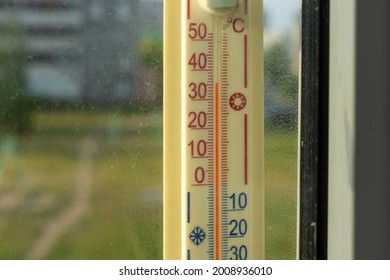 Outdoors thermometer on the window shows a abnormal hot temperature outside