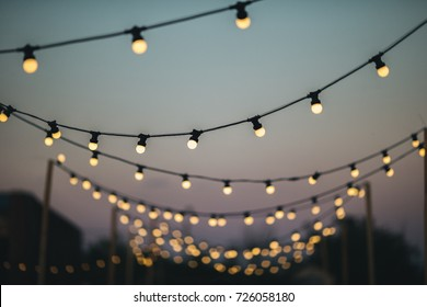 Outdoors wedding decoration with light bulbs at sunset