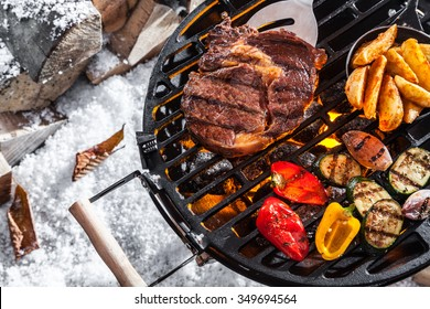 Outdoors winter barbecue with marinated meat and fresh healthy vegetables grilling over the hot coals on a portable BBQ, high angle on snow