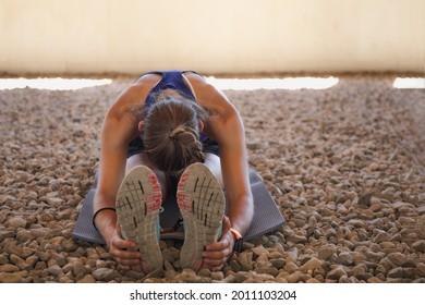 Jóvenes al aire libre haciendo ejercicio de estiramiento en el suelo de piedras en entrenamiento ambiental extremo.