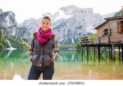 An outdoorsy brunette is smiling, standing with her hands in her pockets. Behind her, the Italian Dolomites are reflected in the still water which provides a mirror reflection of the mountains.