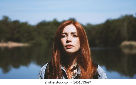outdoorsy young woman standing by lake in harsh light with deep shadows - authentic real people concept