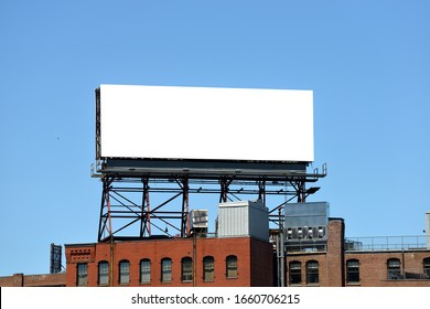 Outdor advertising in the city, mockup. Large billboard on roof top of brick building.