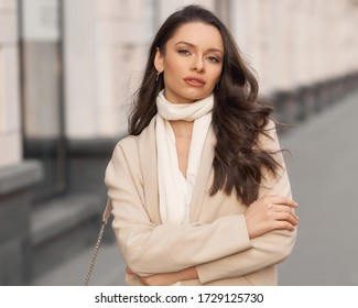 Outdor portrait. Elegant woman in beige jacket with white scarf walking city street holding leather handbag. Pretty female model with long wavy brunette hair and perfect makeup