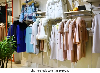 Outer clothing for ladies on hangers at the shop. Women's elegant fashion coat with fur at the store .
