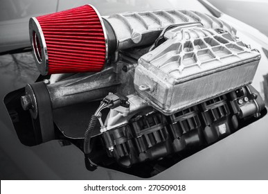 Outer supercharger, air compressor that increases the pressure or density of air supplied to an internal combustion car engine mounted on black hood, closeup photo with selective focus and shallow DOF