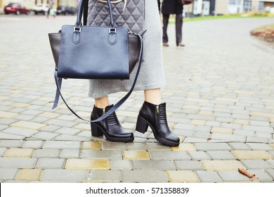 Outerwear, warm clothing. Fashionista. Black ankle boots, dark blue bag, warm coat and knitted dress. Stylish and fashionable girl on a walk.