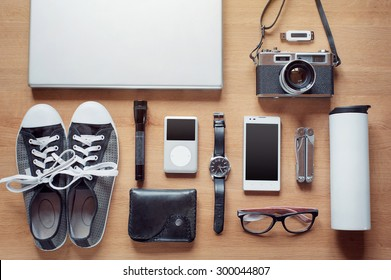 Outfit of modern traveler, student, woman or guy. Overhead of essentials on wooden background: camera, smartphone, glasses, flashlight, laptop, wallet, watch, gumshoes, thermos, mult itool, mp3 player