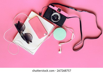 Outfit of student, teenager, young woman or girl . Overhead of essentials for modern young person. Different objects on  pink background . Pastel  tender colors. Area view.
