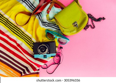 Outfit of student, teenager, young woman or girl . Overhead of essentials for modern young person. Different objects on pink background . Bright summer  colors. Area view.