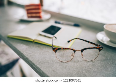 Outfit of student, young woman or girl. Overhead of essentials for modern young person. Different objects on table in coffe shop. Glasses, smartphone, peper notebook. Selective focus. Toned image.