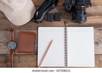 Outfit of traveler to photography. Plan to trip for take photo. Different objects on wooden background. Top view.
