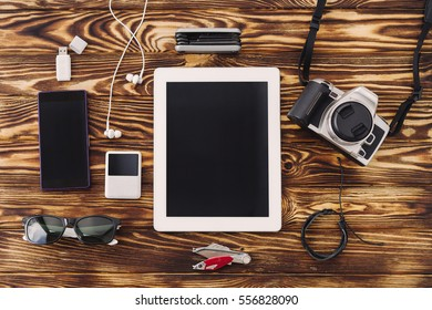 Outfit of traveler, student, teenager, hipster. Top view of essentials for modern young person. Gadgets and accessories on wooden background. Flat lay composition, copy space.