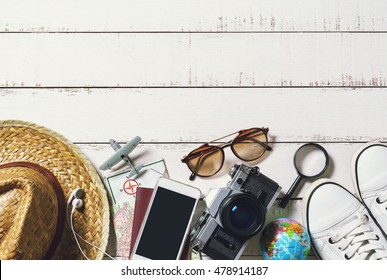 Outfits and accessories of traveler on wooden background, Summer and Travel concept