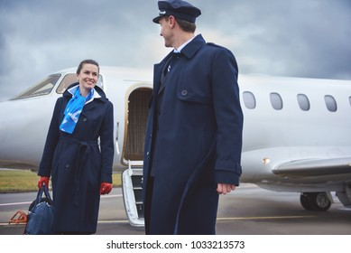 Outgoing air-hostess talking with happy pilot while going at airfield from plain. Communication and occupation concept
