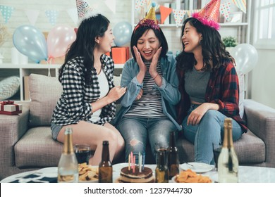 Outgoing friends giving cake with candles to cheerful girl. group of asian ladies relaxing sitting on sofa in decorated room with colorful balloons. Happy birthday surprise concept.