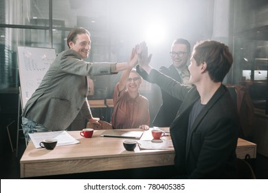 Outgoing girl and beaming men putting arms together while sitting at table in office. Business concept