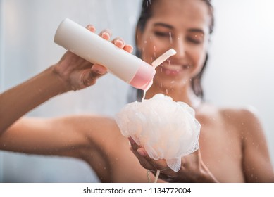 Outgoing girl putting shower gel on puff. She taking hot shower