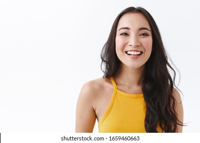 Outgoing, joyful good-looking young modern east-asian woman in yellow top, laughing carefree, smiling and gazing camera happy, making cheerful expression as enjoy nice friendly atmosphere