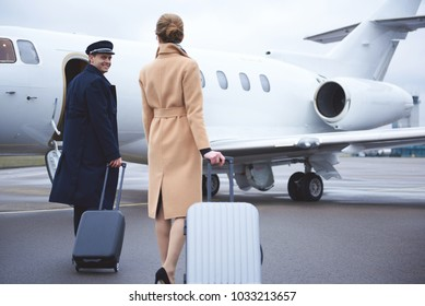 Outgoing pilot telling with businesswoman while moving to aircraft. They holding baggages. Travel concept
