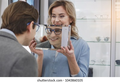 Outgoing smiling male looking at mirror while wearing spectacles. Woman holding it. Clients in optician shop concept