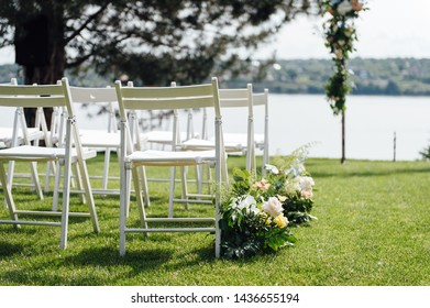 Outgoing wedding ceremony. Decor Studio. white wooden chairs on a green lawn.