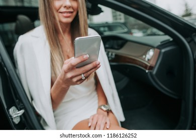 Outgoing woman sending message on phone while keeping it n hand. She sitting in cozy automobile