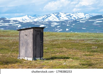 Outhouse toilet with Reindeer symbol used by the indigenous Same People in Padjelanta National Park in Swedish Lapland with Open Landscape and Mountain Range in the distance.