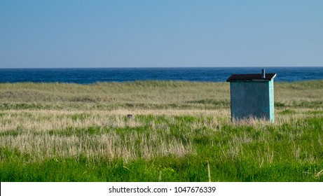 An outhouse/bathroom sits all alone in a green grassy meadow. The deep blue ocean is in the background which meets the blue sky at the horizon. The outhouse is  a wooden structure with a black roof.