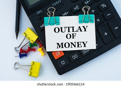 OUTLAY OF MONEY - words on a white sheet with clips on a white background with a calculator, buttons and yellow stationery clips. Business concept
