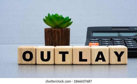 OUTLAY - word on wooden cubes against the background of calculator and cactus. Business concept