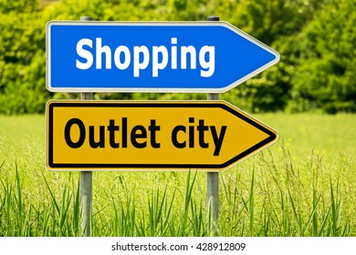 Outlet city Shopping. Yellow road signs with words Outlet city and blue arrow  highway directions signs with word Shopping on green field background, Germany
