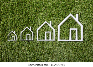 Outline Of An Increasing Size Of House On Green Grass