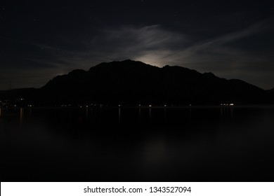 Outline of a mountain behind a calm lake at night. Taken at Attersee, Austria