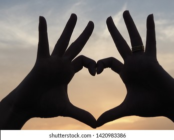 Outline of woman hand making heart shape.