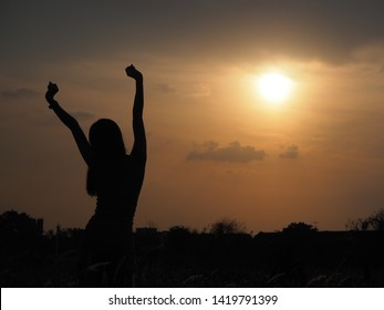 Outline of a woman standing in front of the sun,happiness concept.