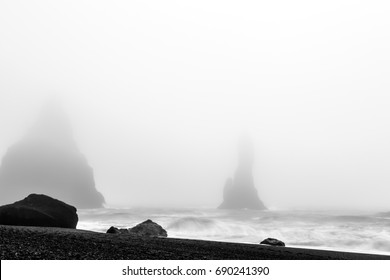 Outlines of basalt sea stacks barely visible in the fog and wild sea spray - Reynisdragar, Iceland