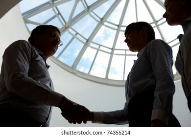 Outlines of business people handshaking after making agreement