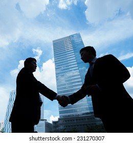 Outlines of businesspeople handshaking after a deal