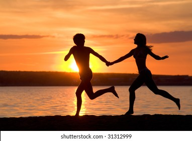 Outlines of happy guy and girl running down seashore at sunset