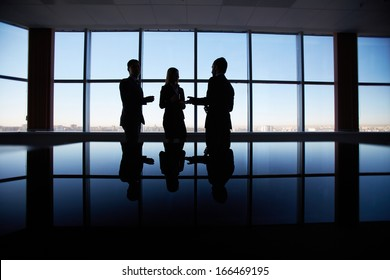 Outlines of three office workers interacting by the window